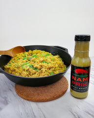 skillet rice with chicken and a bottle of nam prik chili sauce