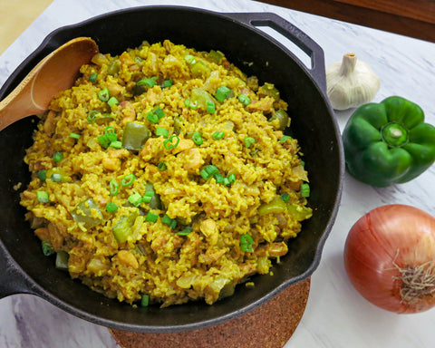 a skillet full of rice with chicken, an onion, green bell pepper, and a bulb of garlic
