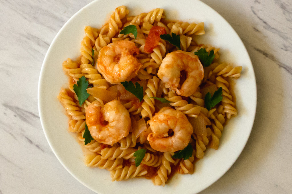 pasta and shrimp in tomato sauce on a plate, centered