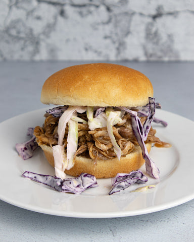 a pulled pork sandwich on a white plate