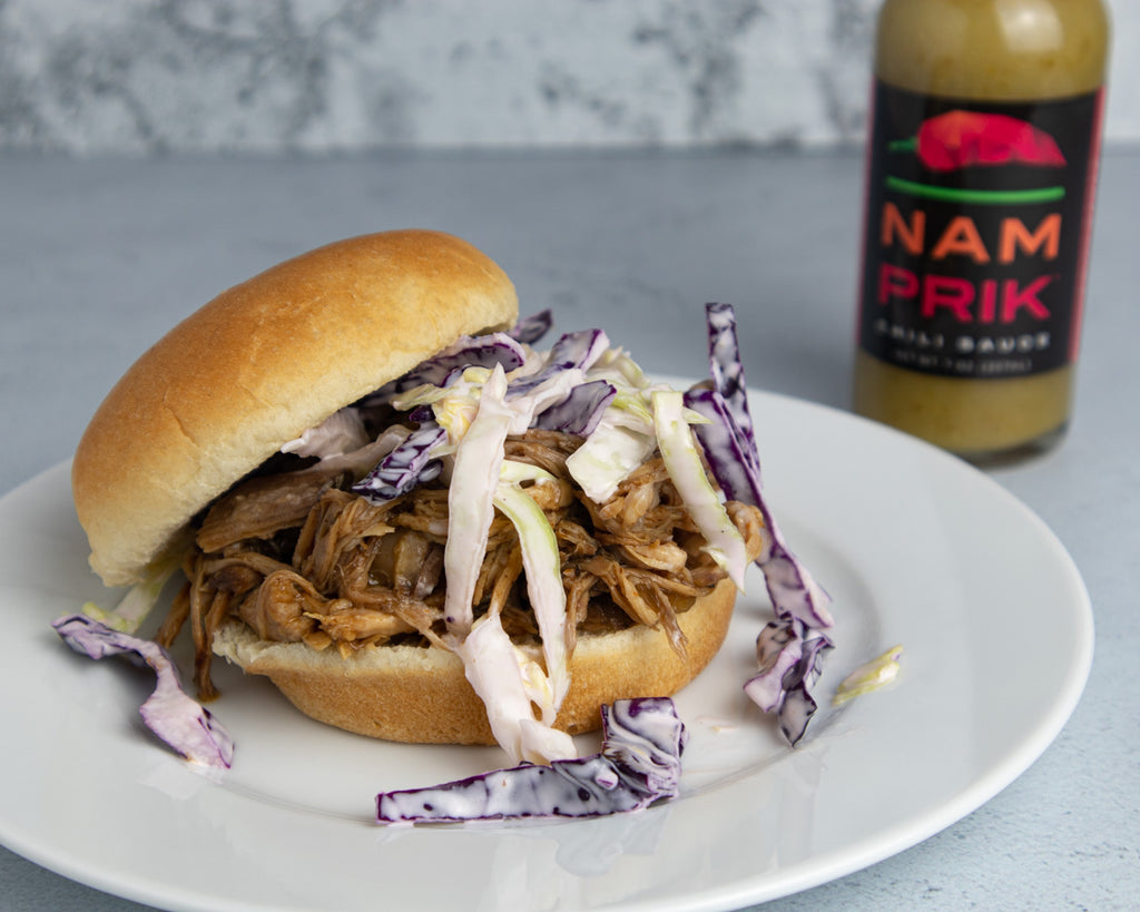 pulled pork sandwich with a bottle of Nam Prik Chili Sauce