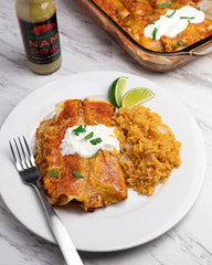 chicken enchilada on a white plate with a bottle of nam prik chili sauce