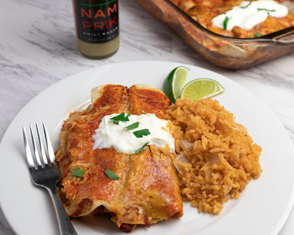 Chicken enchilada on a white plate with Spanich rice and a bottle of nam prik chili sauce in the back