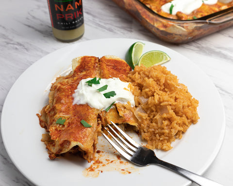 a plate of chicken enchilada with Spanish rice and a bottle of nam prik chili sauce
