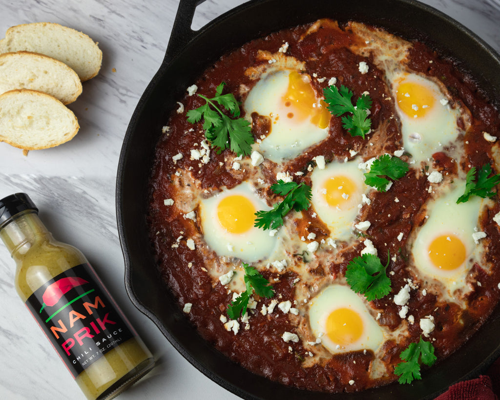 shakshuka in cast iron skillet and a bottle of nam prik chili sauce