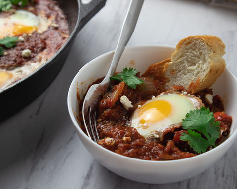 shakshuka in a white bowl with a slice of french baguette