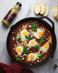 shakshuka in cast iron skillet with a bottle of nam prik chili sauce
