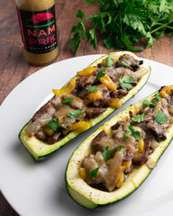 two cheesesteak zucchini boat with a bottle of nam prik chili sauce