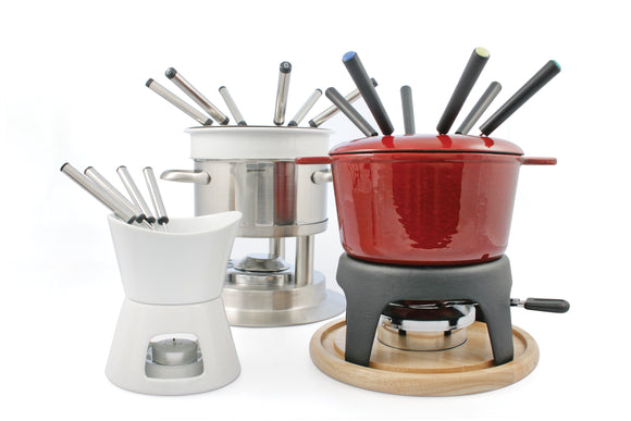 Swissmar Sierra Cast Iron Fondue Set, shows black base and white pot with wooden coaster. Image includes fondue forks and burner.