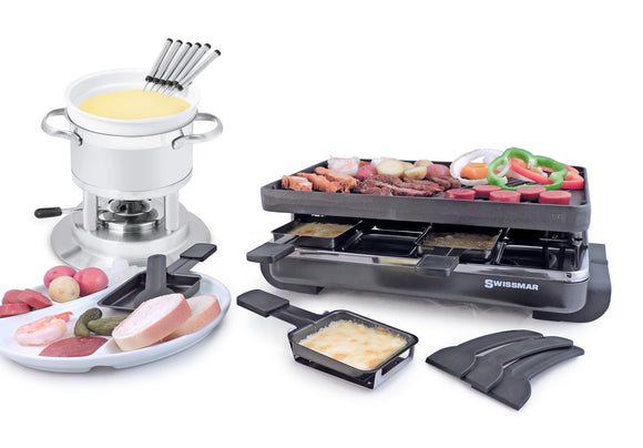 Fondue with cheese and raclette with food on top. There is a plate in front with food on it as well