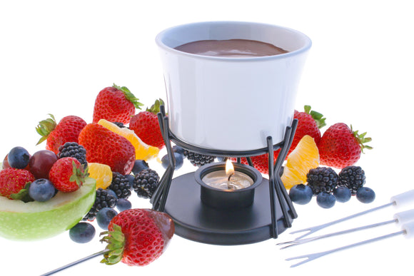 Swissmar Kindle 7 Pc Chocolate Fondue Set with melted chocolate in the fondue and the tealight underneath lit with fruit scattered around