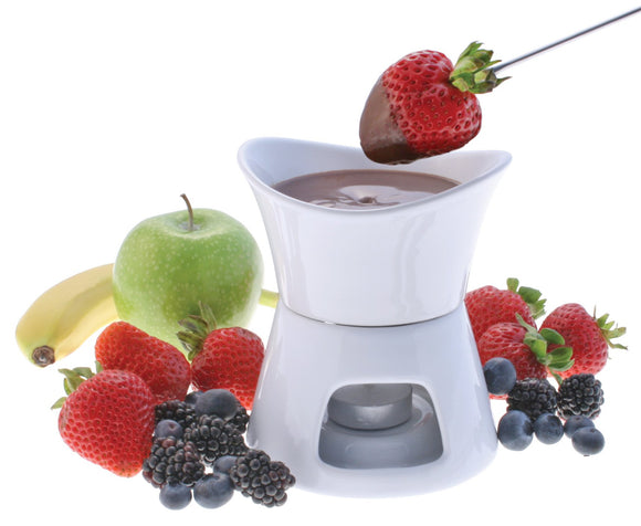 Swissmar Glow 7 Pc Chocolate Fondue Set with melted chocolate, fruit surrounding it and a strawberry on a fork being dipped into the chocolate