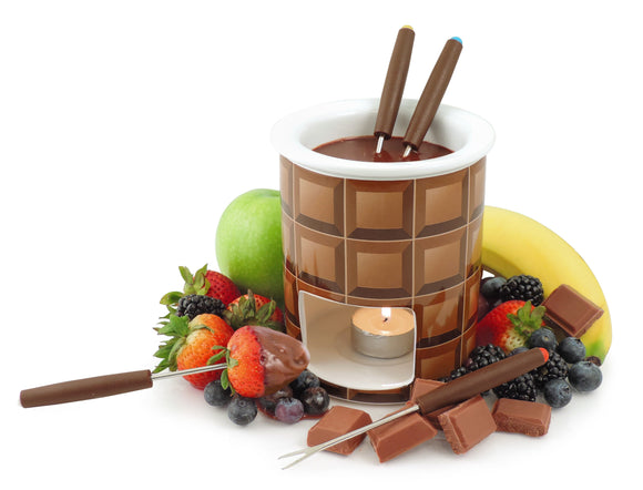 Swissmar Decadence 7 Pc Chocolate Fondue Set product shot with tea light lit inside, melted chocolate inside and fruit spread out around it