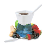 Swissmar Deco 6 Pc Chocolate Fondue Set in blue with tea light lit underneath and melted chocolate inside with fruit spread out around it