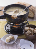 Swissmar Gruyère 9 Pc Ceramic Fondue Set filled with melted cheese. Bread is on the forks and placed on top of and around the fondue pot