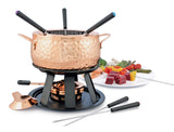 Swissmar Biel 11 Pc Copper Fondue Set with a plate of food in the background