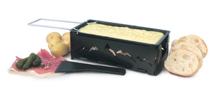 Swissmar Nordic Foldable Candlelight Raclette with melted cheese and bread and meats spread out around the raclette