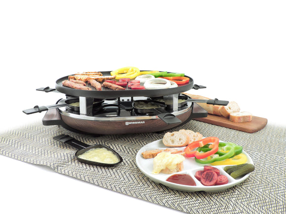 Raclette shown with food on top of grill, melted cheese in raclette dishes in front of raclette and a plate full of food in front