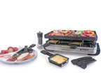Raclette shown with food on top of grill, melted cheese in raclette dishes in front of raclette and a plate full of food to the left