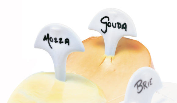 Swissmar Cheese Flags with cheese names written on them, sticking out of cheese