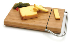 Swissmar Bamboo Board with Cheese Slicer Blade with sliced cheese on top
