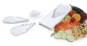 Borner V-Slicer White Plus Mandoline White with Safety Holder and inserts spread out with sliced vegetables in the background