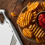 photo of a bowl of lattice cut fries with the Börner White PowerLine Wave Waffle Cutter showing partially in the bottom left corner