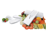 Swissmar V-Prep™ Mandoline Slicer with all inserts, storage box and safety holder spread out and vegetables spread around