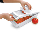 Swissmar V-Prep™ Mandoline Slicer in use over top of storage container with the food sliding into the container