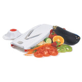 Vslicer in white with safety holder on one side and assorted sliced vegetables on the other side