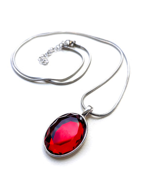 Store version of Anna's necklace made of a silver nickel and lead free zinc alloy with a blood red oval-cut stone with a stainless steel chain, comes wrapped in black paper in a high quality tin box