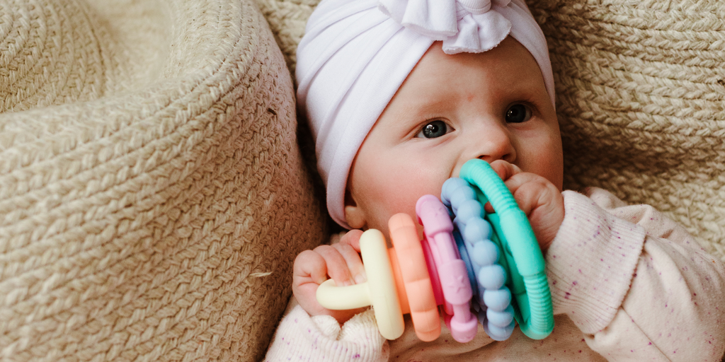 Baby Girl Chewing on Pastel Stacker.