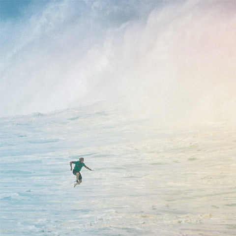 Jamie O'Brien jumps off his board as a huge wave rushes toward him