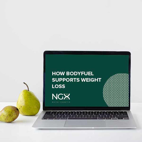 """A white desk with a pear standing up next to a laptop which says """"How BodyFuel supports weight loss"""""""