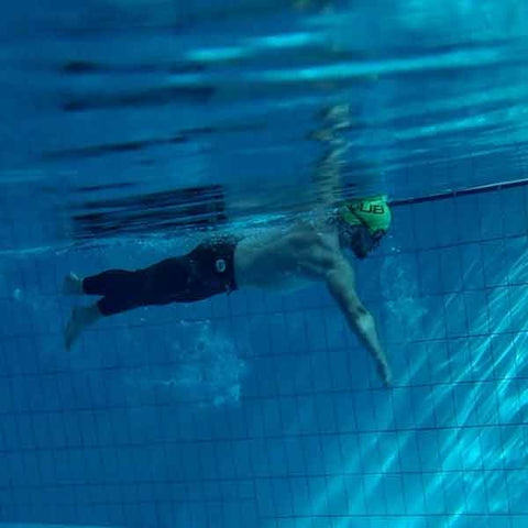Underwater photo of man swimming in a green cap and full length neoprene trousers.