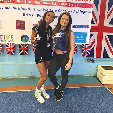 Two girls, one on the left holding a Powerlifting trophy.
