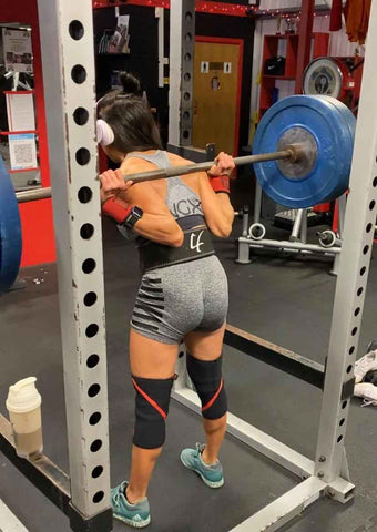 Female squatting with an NGX sports bra on and shorts
