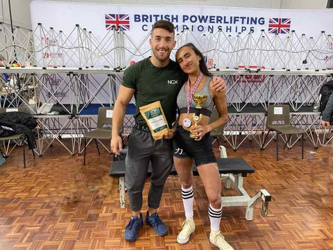 Women holding weightlifting trophy next to a man.
