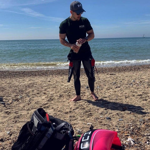 Man standing on the beach with a hat on, NGX top and wetsuit holding an NGX shaker.