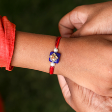 Load image into Gallery viewer, Blue Kundan Rakhi with Shades of Red Thread