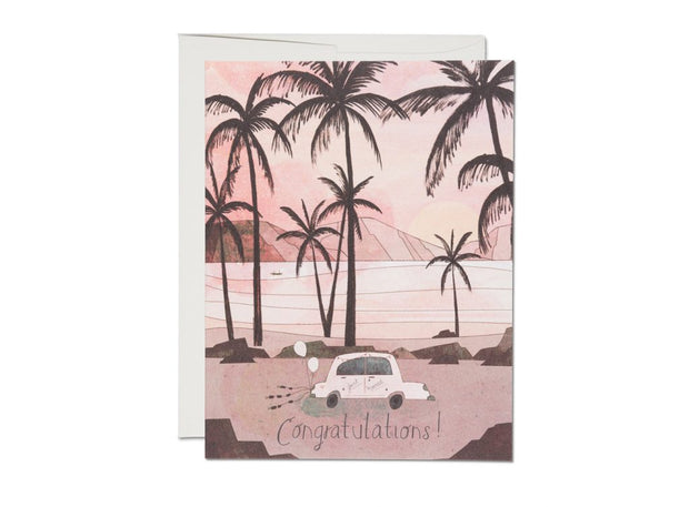 Congratulations card with a white car that says just married on the side and has balloons and tin cans attached to the back. Palm trees and the ocean are in the background.