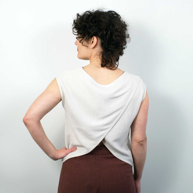 back of a slightly cropped blouse, model has hand on her hip and the sand colored blouse features a petal back.