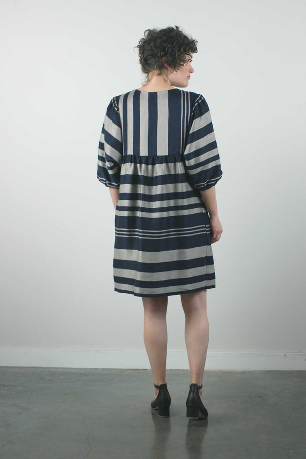 "knee length perpendicular striped dress with balloon sleeves and loose waist by jennifer glasgow on a 5'3"" model with short brown hair and short heels, standing with back of dress to the camera"