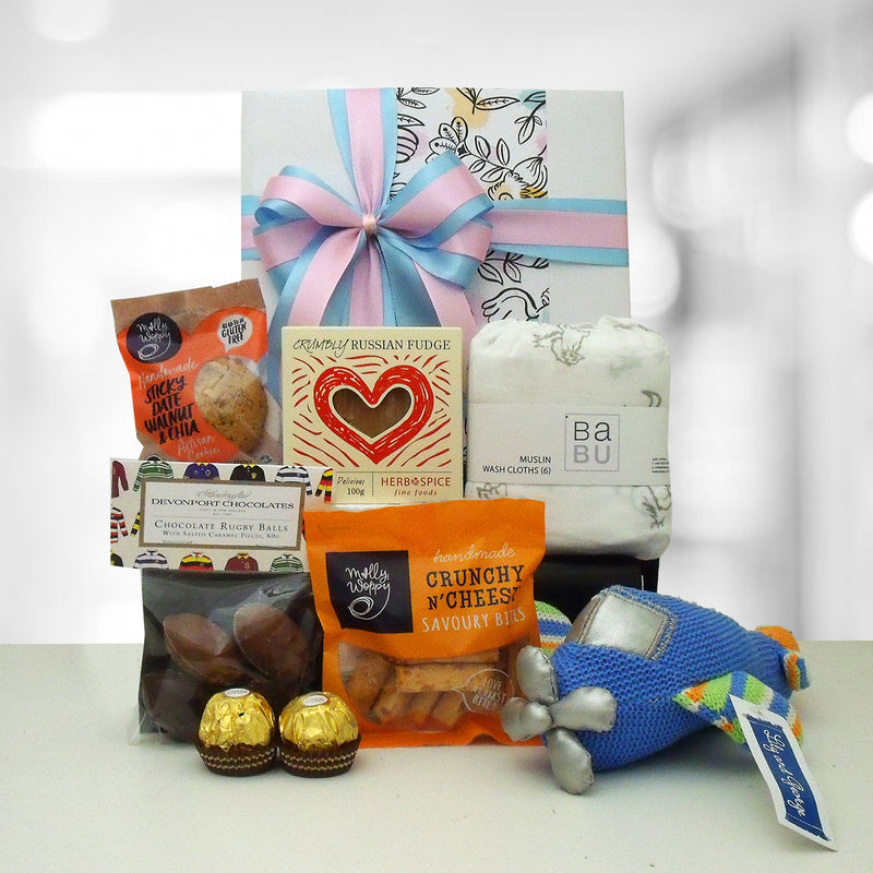 Baby gift hamper with knit plane, muslin wash clothes, chocolate and nibbles.