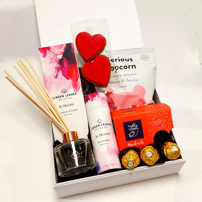 In Bloom gift basket with room diffuser, bath bombs, gingerbread, cookies and popcorn all presented in a modern gift box.