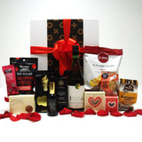 Valentines Day gift hamper for her with wine, bath salts, hand cream, rose petals, chocolate and more presented in a modern gift box.