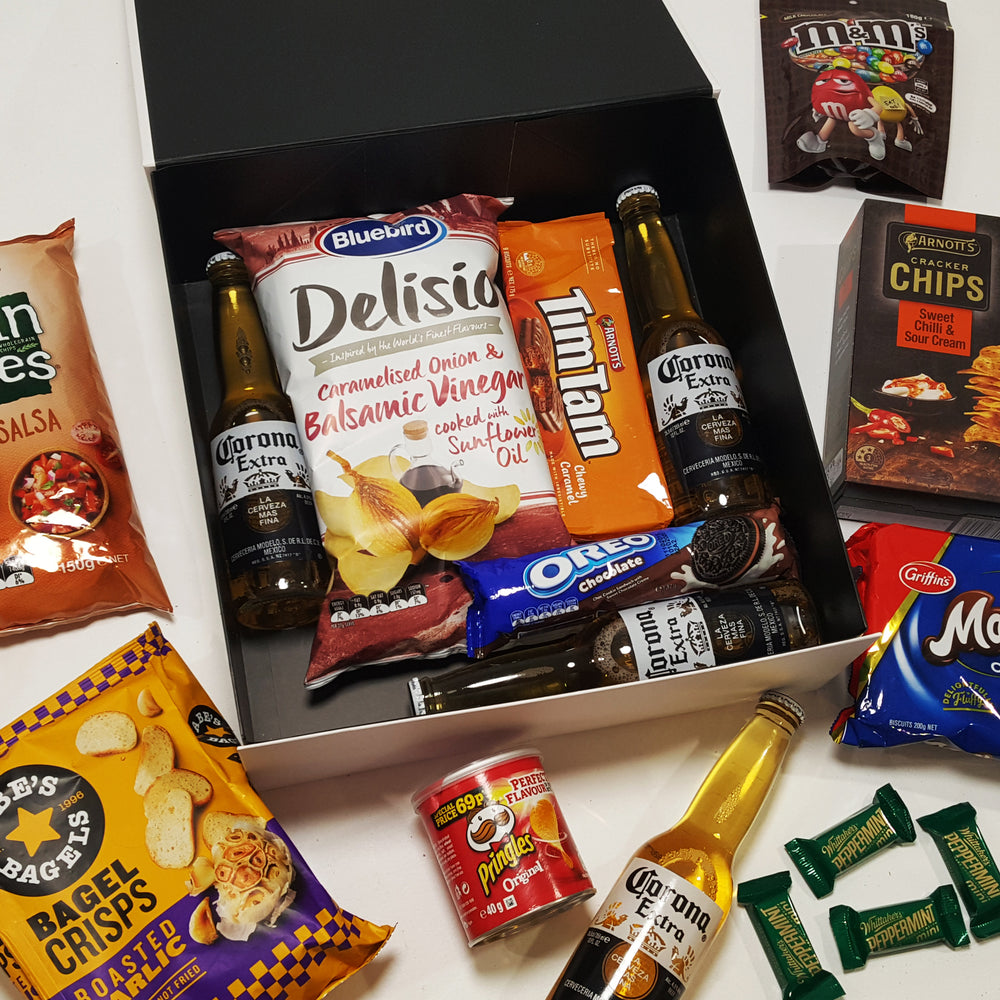 Brews & Bites Gift Basket with Grain Waves, Bagel Crisps, Whittakers, Tim Tams, Corona & more all presented in a modern gift basket.