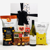 Cheers gift hamper with wine, popcorn, chocolate, fudge, brownie & nuts presented in a beautiful Gift Box.