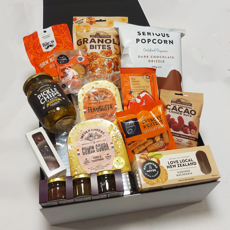 Craving crusher gift basket with cheese, pickles, chocolate, popcorn, cookie and more all presented in a modern gift box.