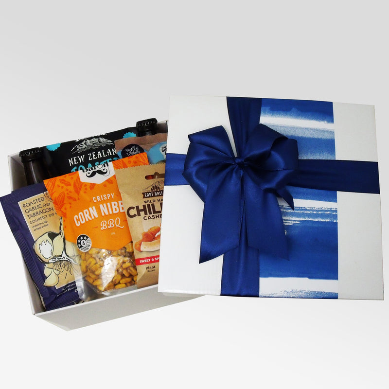 Blue themed gift basket for him filled with 2 craft beers, nuts, chocolate, cookie and a dip.